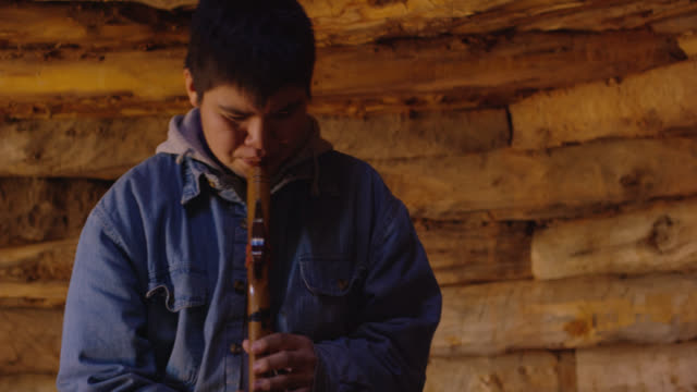 a teenaged native american boy plays a navajo flute in a hogan (navajo hut) - native american reservation stock videos & royalty-free footage