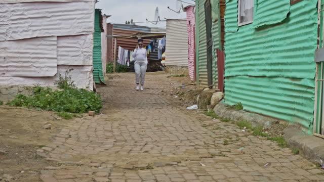タウンシップ通りに歩いてティーンエイ ジャー ブラックの女の子 - 掘建て小屋点の映像素材/bロール