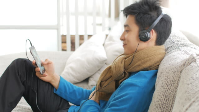 ティーンエイ ジャーの男の子のソファの上の音楽を聴いて楽しむ時間、ライフ スタイルをリラックス、リラクゼーション コンセプト、パンに右左移動