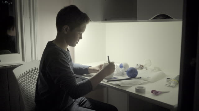 vídeos y material grabado en eventos de stock de teenager boy in bedroom painting globe - un solo adolescente