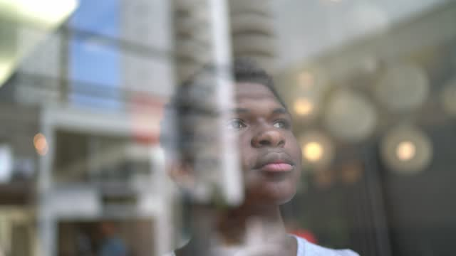 teenager boy looking through window contemplating at home - one teenage boy only stock videos & royalty-free footage