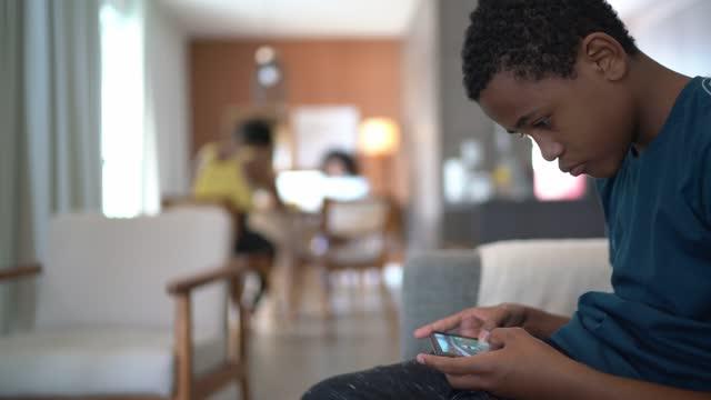 tonåring pojke spelar på smartphone hemma - profil sedd från sidan bildbanksvideor och videomaterial från bakom kulisserna