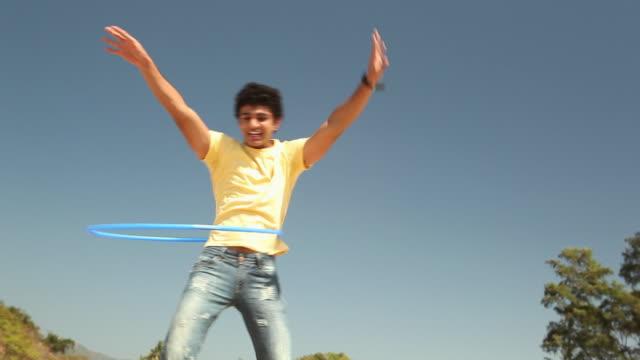 teenager boy playing with hula hoop on the beach - männlicher teenager allein stock-videos und b-roll-filmmaterial