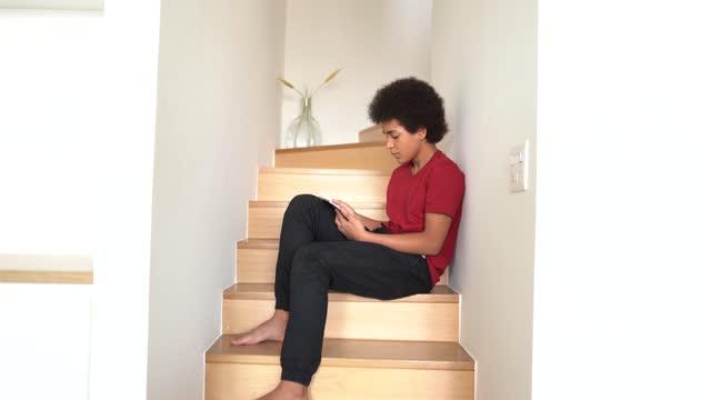 stockvideo's en b-roll-footage met teenager boy sitting on the stairs using digital tablet at home - 14 15 jaar