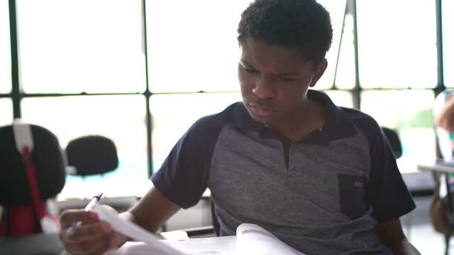 vidéos et rushes de adolescent qui passe un test à l'école ou à l'université - détermination intérieure