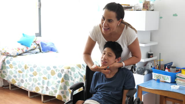 teenager boy with celebral palsy at home, massaged by mother - co ordination stock videos & royalty-free footage