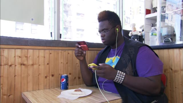 vídeos de stock, filmes e b-roll de / teenager buys and eats pizza and a soda at a bronx ny pizza parlor / sits down and immediately uses cell phone and ipod while eating pizza and... - preocupação com o corpo