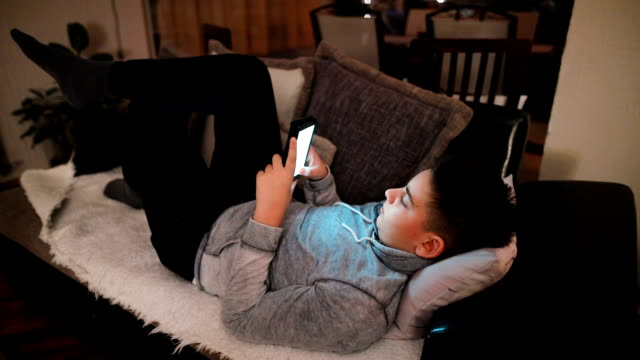 teenager chatting with friends on smartphone lying on couch, social network - sending stock videos & royalty-free footage