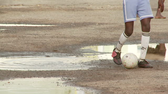 a teenager dribbles a soccer ball on a dusty field in ghana. available in hd. - ghana stock videos and b-roll footage