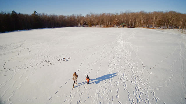 Teenager girl and little boy running on the snow. Slow motion aerial footage. The Poconos, Pennsylvania, USA