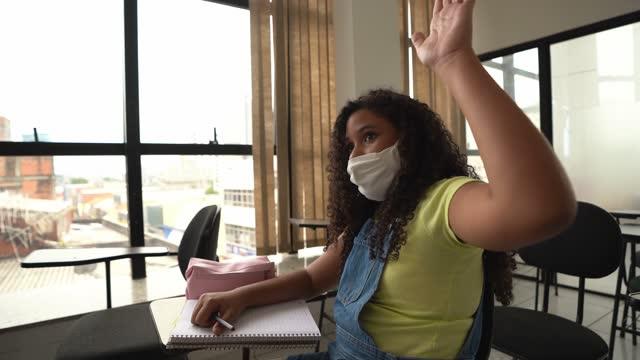 vídeos de stock, filmes e b-roll de adolescente fazendo pergunta durante aula na escola - usando máscara facial - de braço levantado
