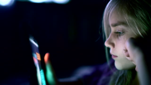 teenager girl browsing social media from the tablet at night in the bed - blond hair stock videos & royalty-free footage