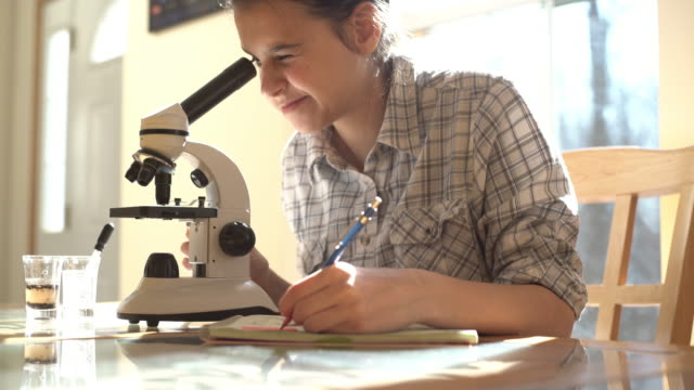 vídeos y material grabado en eventos de stock de chica adolescente haciendo laboratorio trabaja con microscopio - a la izquierda de
