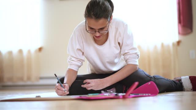 vídeos de stock e filmes b-roll de teenager girl draws, sitting on the floor in the living room - 14 15 years