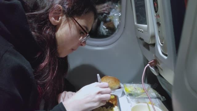 vídeos de stock e filmes b-roll de teenager girl eats on board of the international flight - aviation fatigue