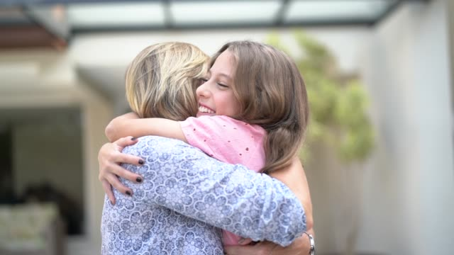 stockvideo's en b-roll-footage met tiener meisje omarmen haar oma in de voorkant van een huis - voor of achtertuin