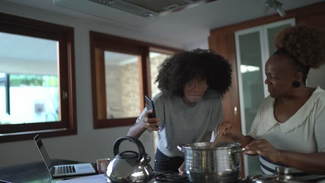 vídeos de stock, filmes e b-roll de adolescente filmando mãe cozinhando em casa - film moving image