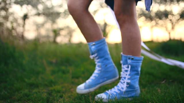 Tonåring flicka håller lång papper och promenader i långa blå canvas sneakers