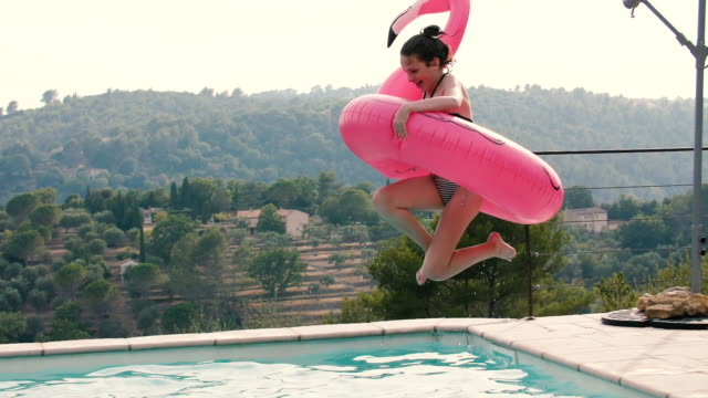 Teenager girl jumping into the pool in slow motion with a pink inflatable flamingo