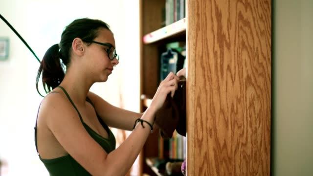 vídeos de stock e filmes b-roll de teenager girl make order on the bookshelf in the living room - 14 15 years