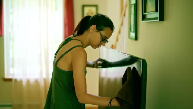 vidéos et rushes de fille adolescente rendre l'ordonnance sur l'étagère dans la salle de séjour - 14 15 years