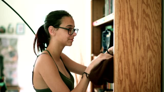 Teenager girl make order on the bookshelf in the living room