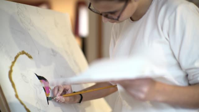 stockvideo's en b-roll-footage met tiener meisje schilderen op het papier vast op de ezel. - 14 15 years