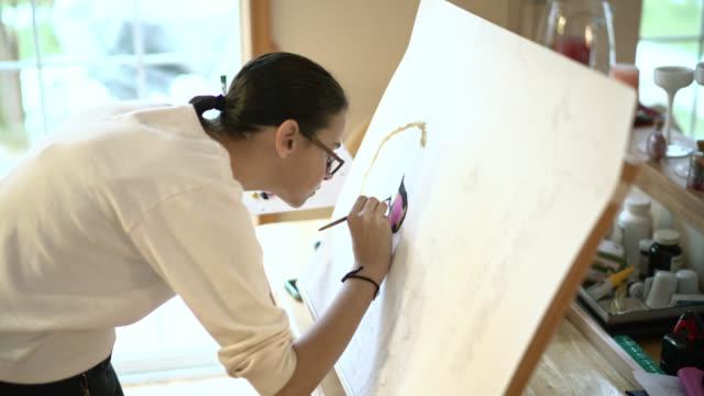 vídeos y material grabado en eventos de stock de chica adolescente pintura sobre papel fijado sobre el caballete. - 14 15 years