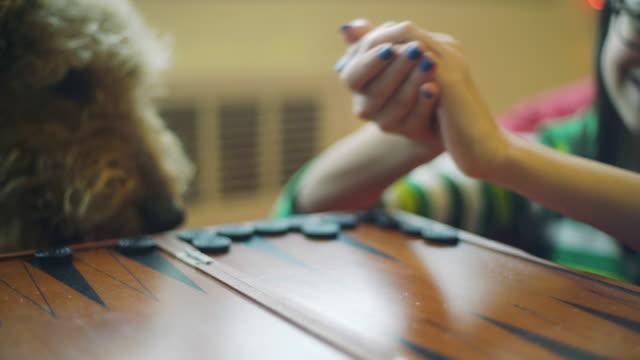 vídeos y material grabado en eventos de stock de chica adolescente divertirse backgammon, tirando de dados - sólo una adolescente