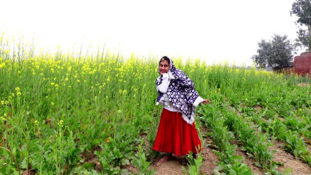 Portrait de jeune fille adolescente près de champ de culture de moutarde