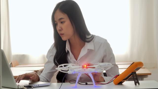vidéos et rushes de robotique de programmation de fille d'adolescent à l'ordinateur portatif dans la salle de classe. femmes d'ingénieur développant le drone électronique. innovation, éducation, technologie, science et concept de personnes. education topics.industry 4.0. - ingénieur