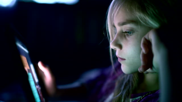 Fille d'adolescent de tablette de lecture pendant la nuit dans le lit