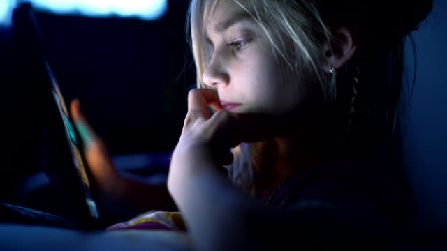 teenager girl reading from tablet at night in the bed - teenage girls stock videos & royalty-free footage