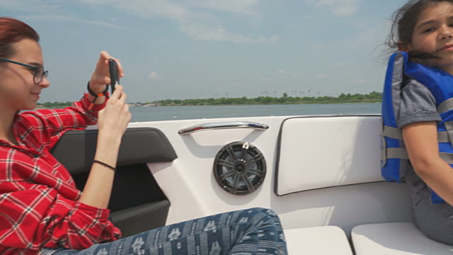 teenager girl riding motorboat in the sunny summer day. using a smartphone to take pictures. - life jacket stock videos & royalty-free footage