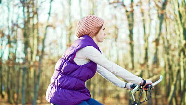 秋の森の道で自転車に乗って 10 代の女の子
