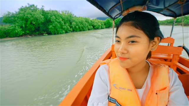 Teenager girl sailing on a long tail thailand boat  through the mangrove forest in southern Thailand