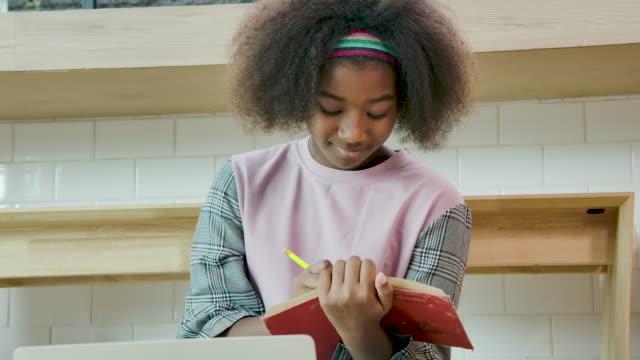 vidéos et rushes de fille d'adolescent étudiant à la maison - détermination intérieure
