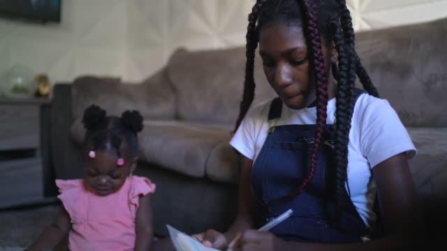 stockvideo's en b-roll-footage met het meisje dat van de tiener thuis bestudeert - zus