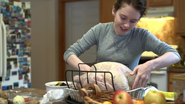 vídeos y material grabado en eventos de stock de chica adolescente relleno el pavo para una cena familiar de vacaciones. - goose meat