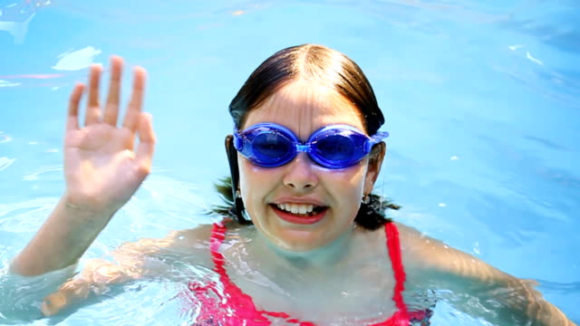 teenager girl swims and waves - swimming goggles stock videos & royalty-free footage