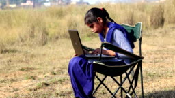 Teenager girl using laptop outdoor in nature
