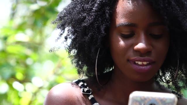 vídeos de stock, filmes e b-roll de menina adolescente usando móveis - afro americano