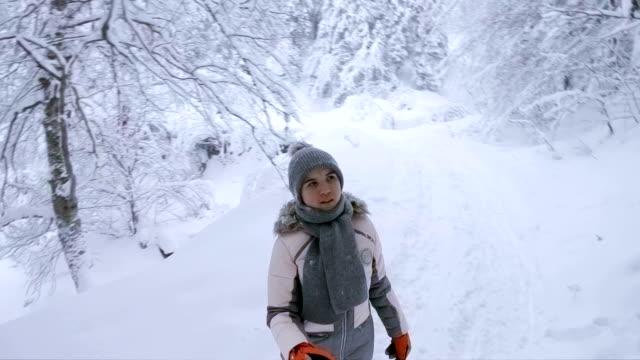 Teenager-Mädchen, die zu Fuß in der verschneiten Winterwald