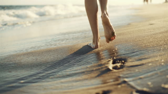 Teenager girl walking on the sandy beach next to the water edge, with closeup planes of legs and footprints