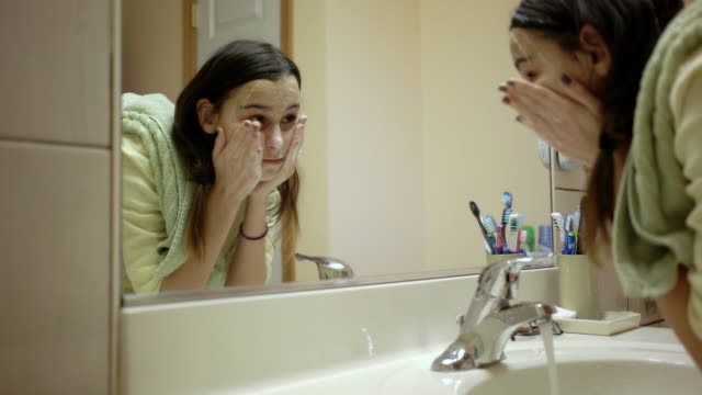 Teenager girl washing face in the domestic bathroom