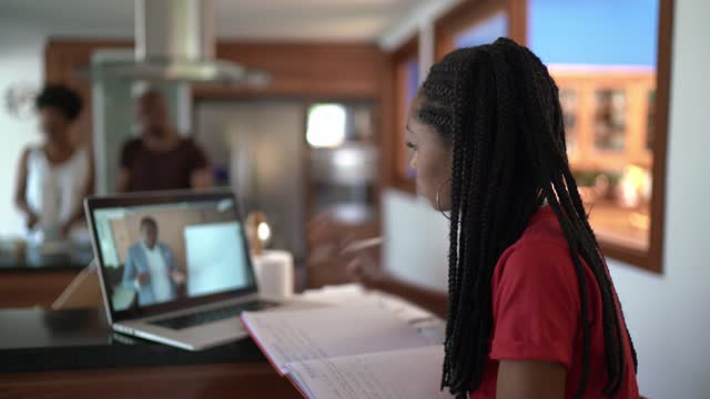 teenager girl watching class on laptop in the kitchen at home - guidance stock videos & royalty-free footage