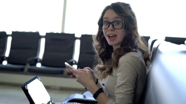 vídeos y material grabado en eventos de stock de niña adolescente con el smartphone y la tableta en el salón del aeropuerto - sólo una adolescente