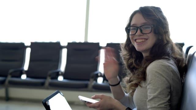 tonåring flicka arbetar med smartphone och surfplatta i flygplatslounge - endast en tonårsflicka bildbanksvideor och videomaterial från bakom kulisserna