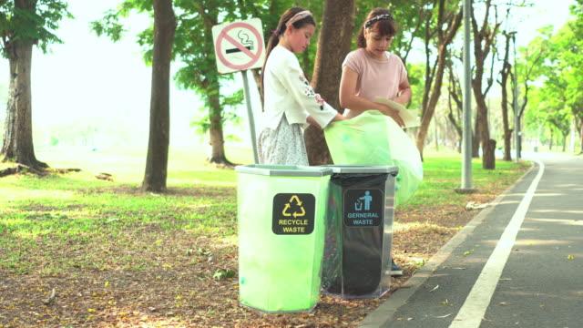 teenager-mädchen helfen, recycelbare abfälle wie flasche in papierkorb im park zu trennen - teilen stock-videos und b-roll-filmmaterial