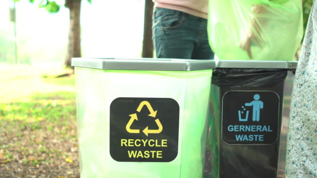 teenager girls'hand help to sepearate recyclable waste  such as bottle into recycle bin in park - waste management stock videos & royalty-free footage